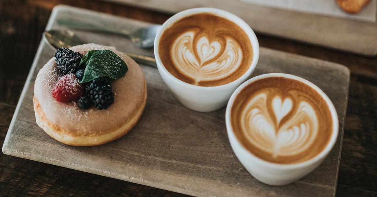 bolle og to kaffekopper på et serveringsbrett i tre