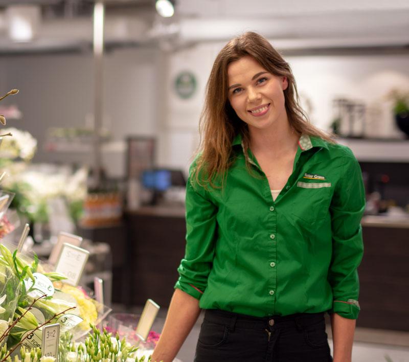 Kvinnelig ansatt hos Mester Grønn med butikken i bakgrunnen og blomster på venstre side