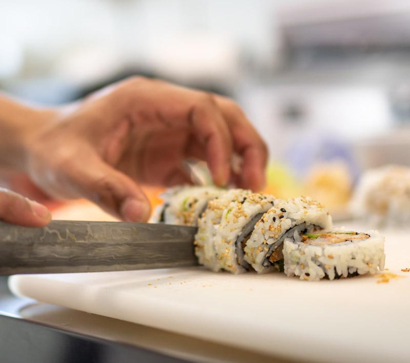 Sushi biter blir skåret på et brett