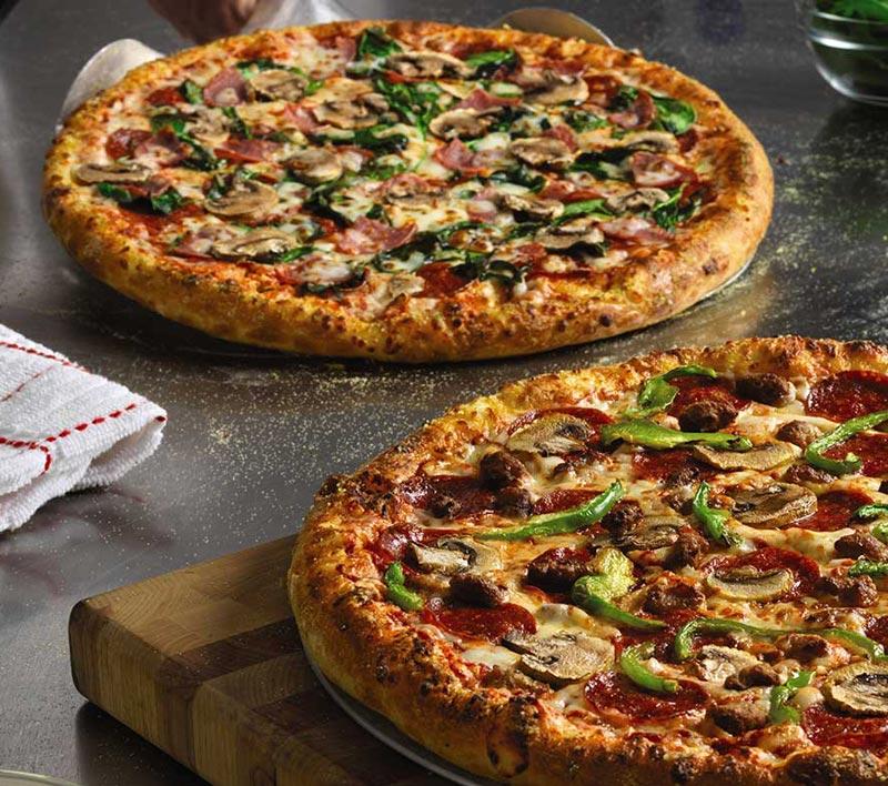To nystekte pizzaer på serveringsbord