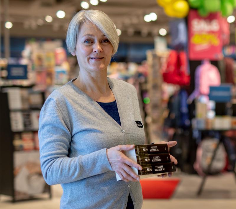 Kvinnelig ansatt hos Norli holder bøker med butikken i bakgrunnen