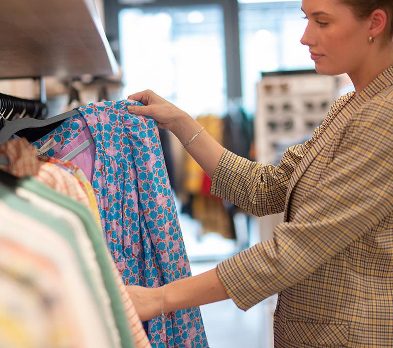 Dame ser på klær i klesbutikk